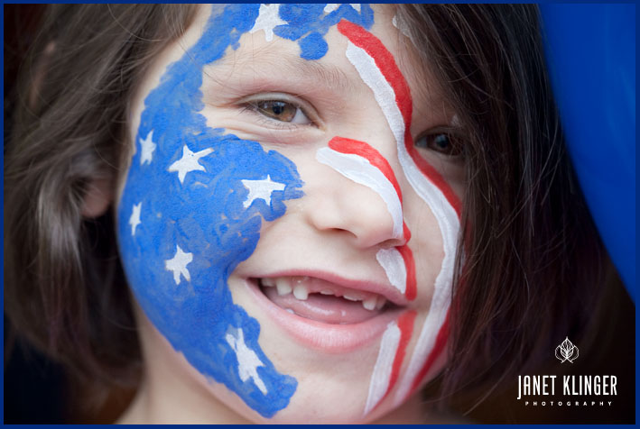 Child celebrates 4th of July with Red, white and blue face painting, and 2 missing front teeth